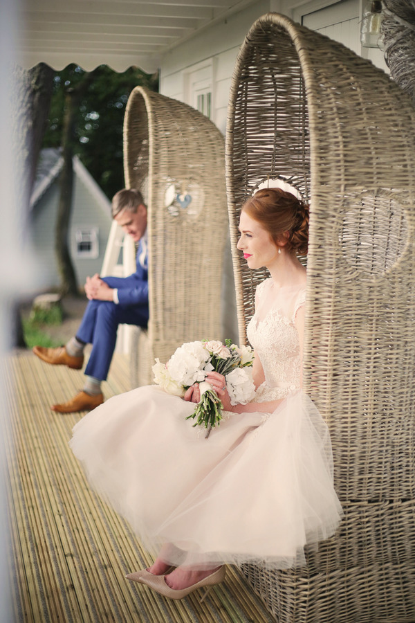 Bride and groom sitting on chairs outside house at Woodhill Hall