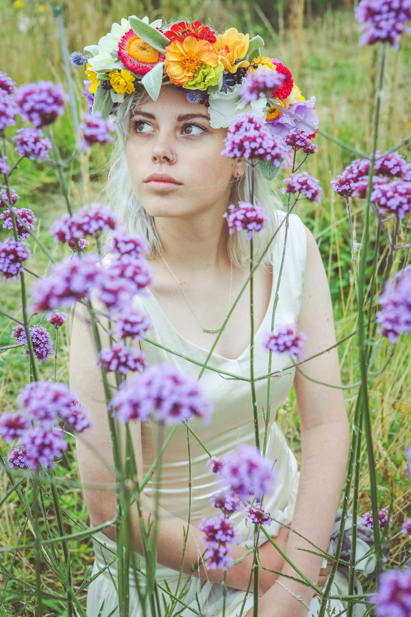 Bride sitting in field of purple flowers