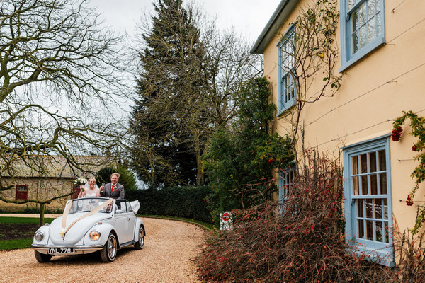Bride and groom arriving at South Farm in convertible Beetle