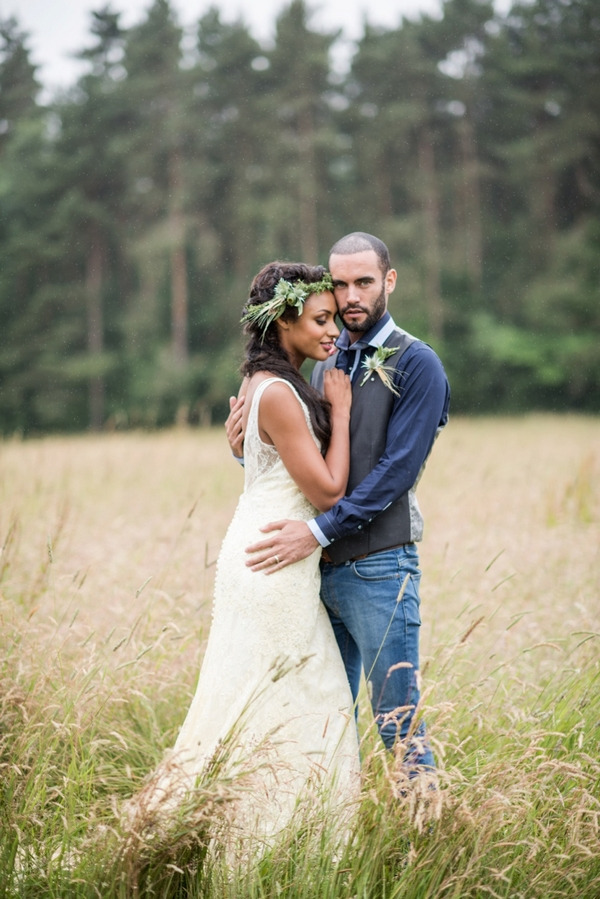 Bride with rustic flower crown standing with groom in meadow