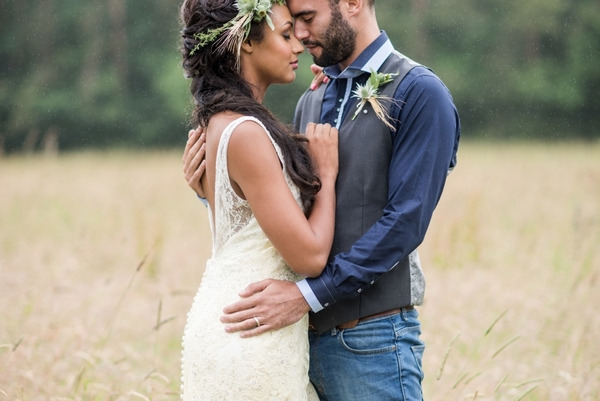 Bride and groom facing each other in meadow resting heads
