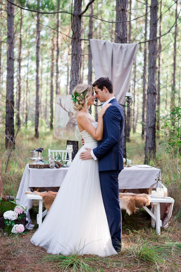 Bride and groom standing in front of wedding table in woodland
