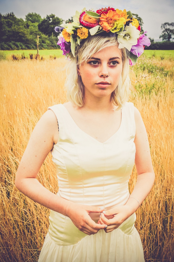 Bride with flower crown standing in front of field