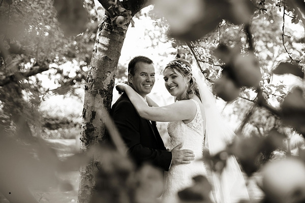 Bride and groom standing under tree