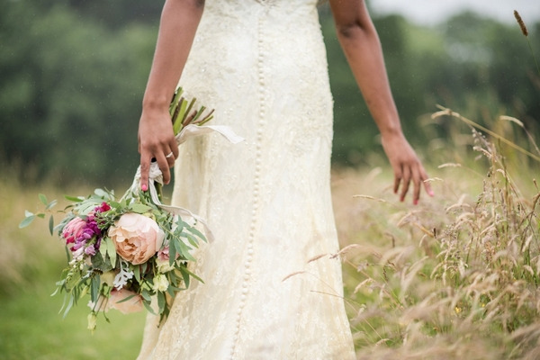 Bride walking with rustic bouquet through meadow
