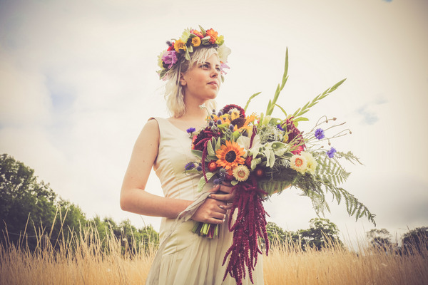Bride with flower crown holding bouquet in front of field