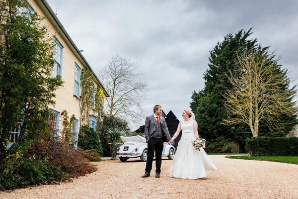 Bride and groom holding hands outside South Farm, Royston