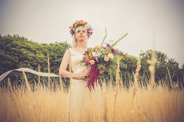 Bride with flower crown holding bouquet in field