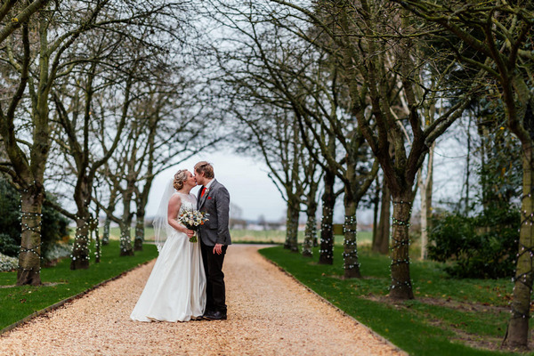 Bride and groom kissing on driveway of South Farm, Royston