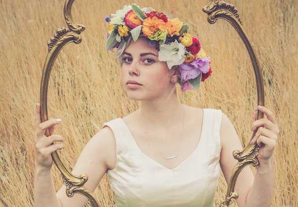 Bride with flower crown looking through frame