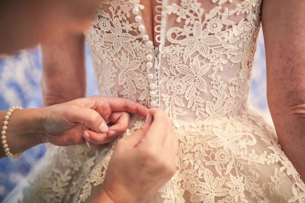 Doing up back of bride's wedding dress