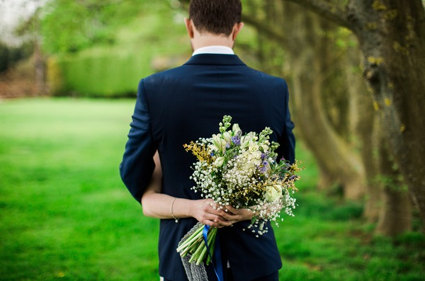 Bride holding rustic bouquet behind groom's back
