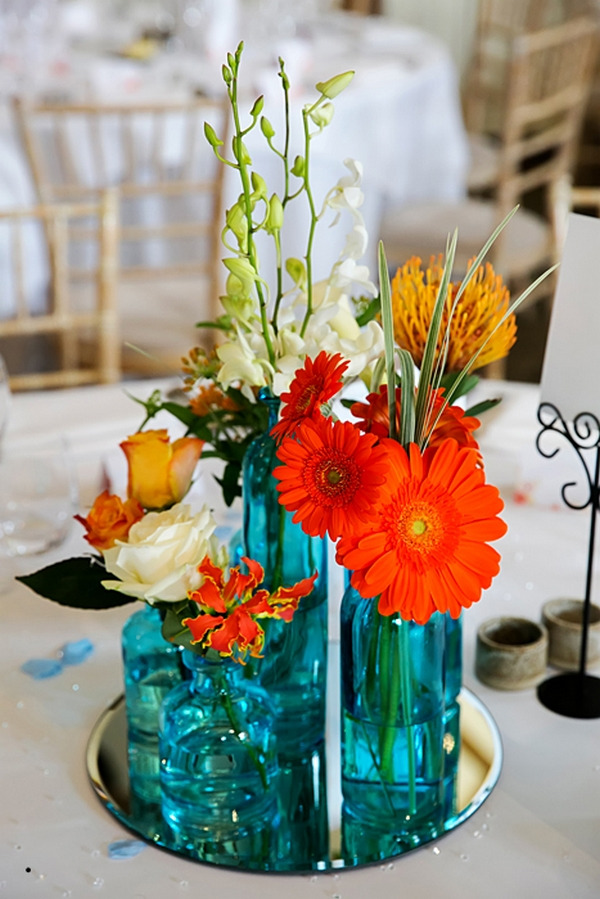 Orange flowers in blue glass vases