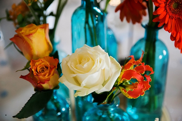 Orange and white flowers in blue vases