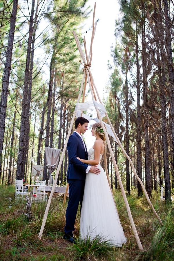 Bride and groom standing under tipi frame