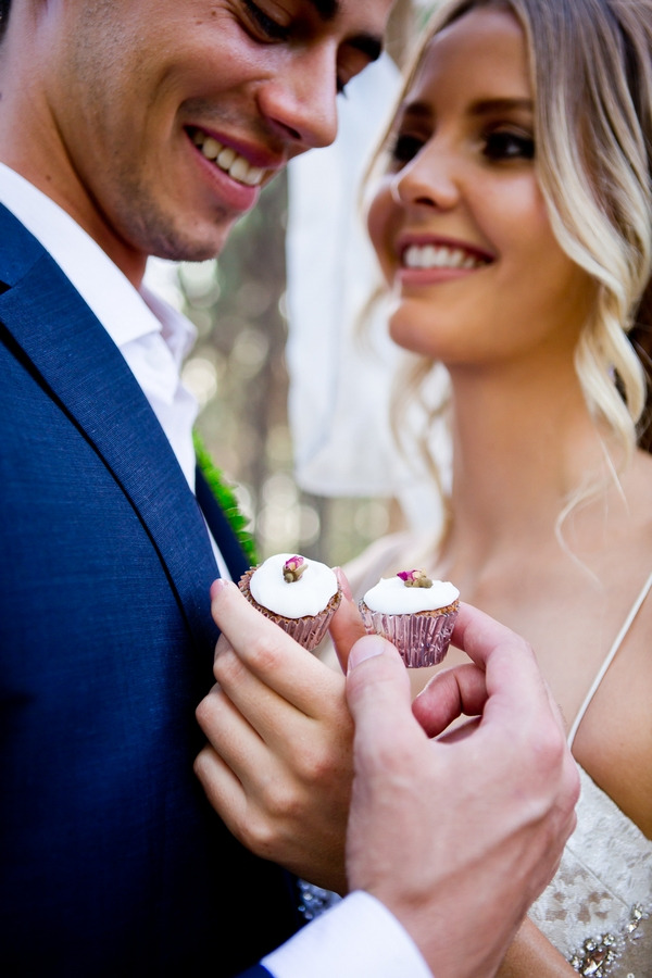 Bride and groom holding small cupcakes