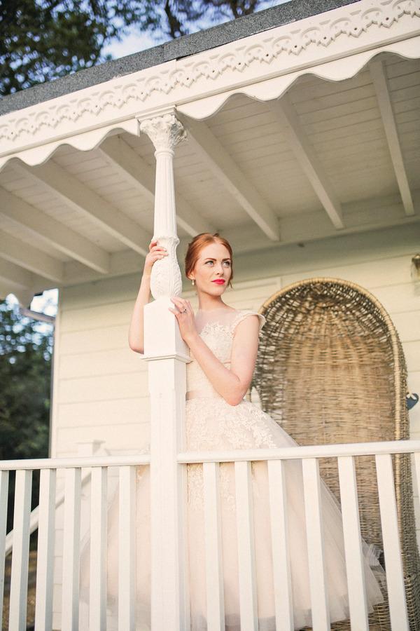 Bride leaning against pillar