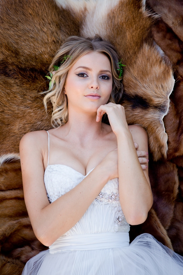 Bride laying on fur looking into camera