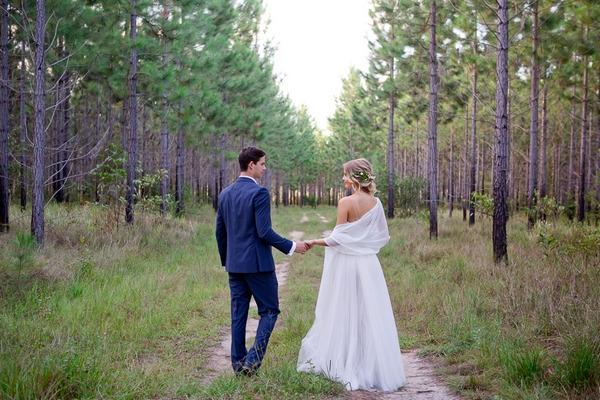 Bride and groom walking in woodland