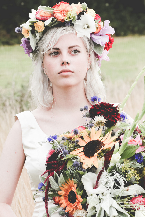 Bride with flower crown holding rustic bouquet