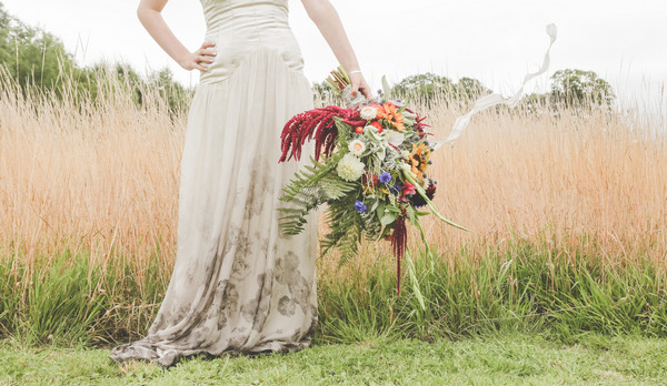 Bride by corn field holding large rustic bouquet