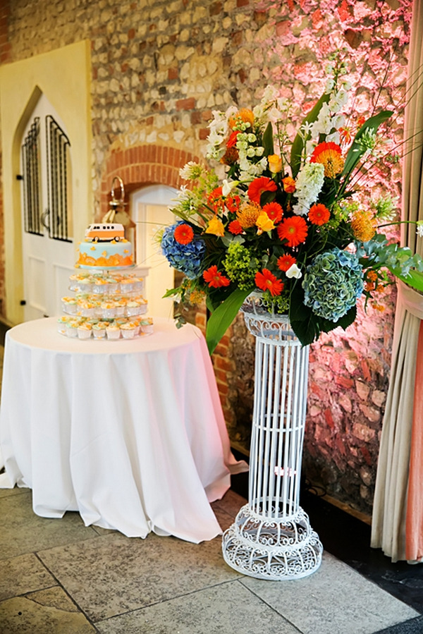Colourful wedding flowers next to cake table