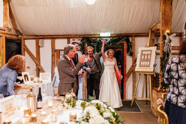 Bride and groom entering wedding reception at South Farm, Royston