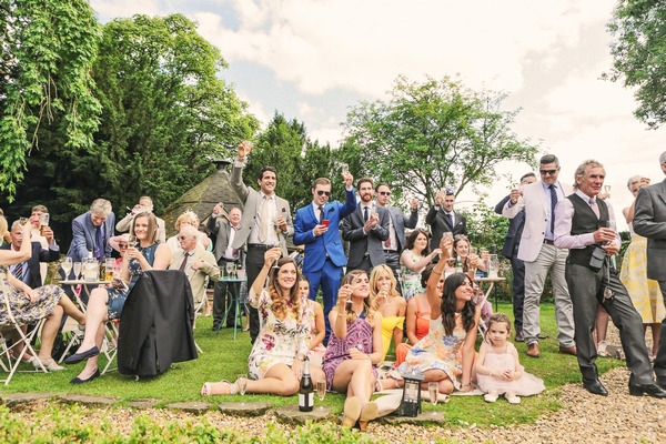 Wedding guests sitting on grass