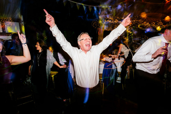 Man dancing with arms up at wedding