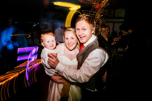 Bride and groom with son on dance floor