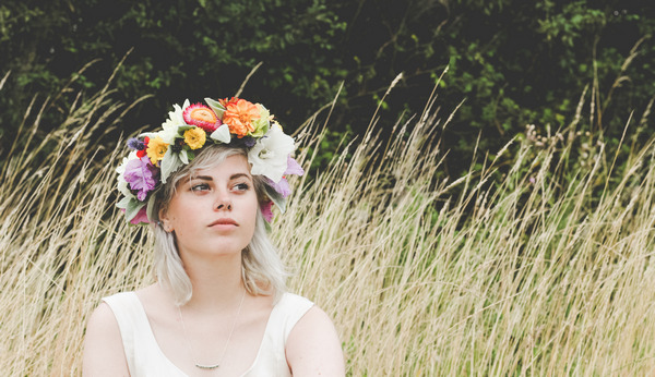 Bride wearing flower crown sitting in field