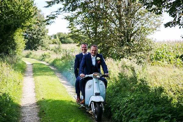 Groom and best man going to wedding on Vespa scooter