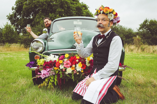 Man with flower crown kneeling in front of Morris Minor