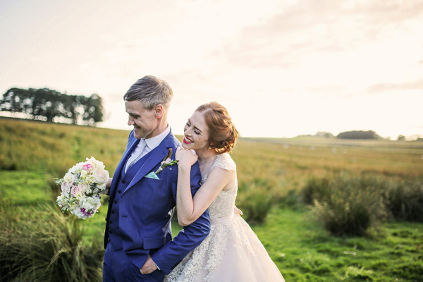 Happy bride leaning on groom in countryside