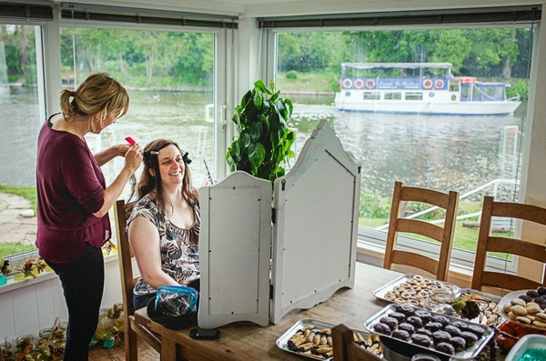 Bride looking in mirror as she has her hair done