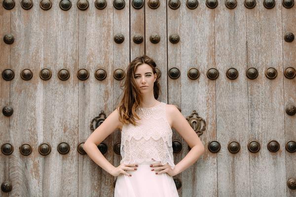 Bride with hands on hips standing against large door