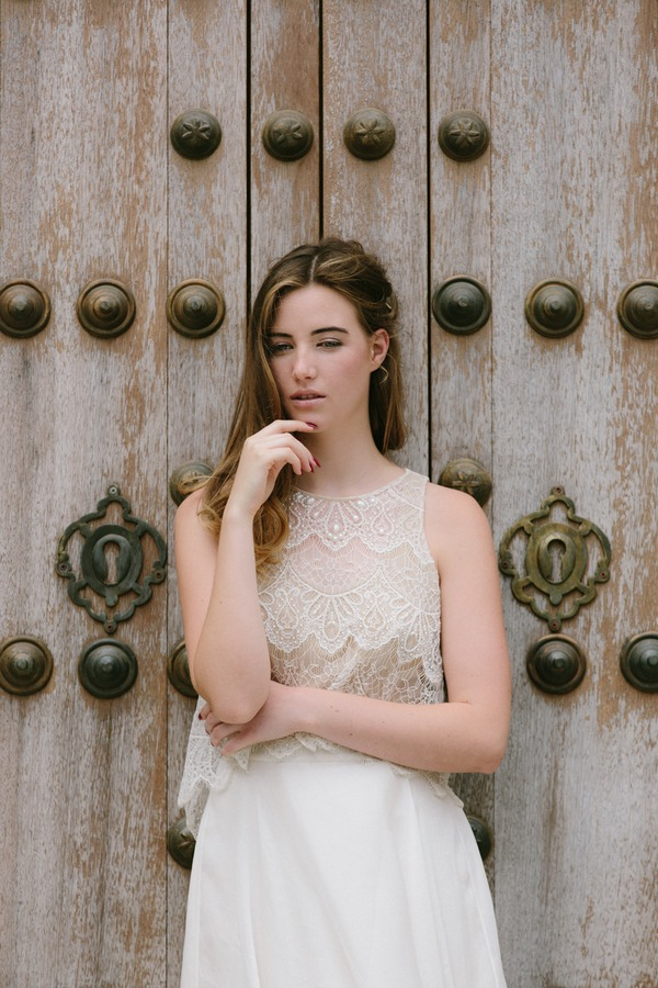Bohemian bride standing against door