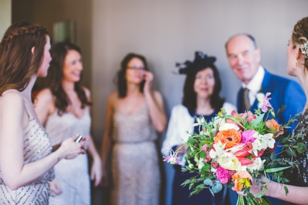Bride holding bouquet with bridesmaids and father