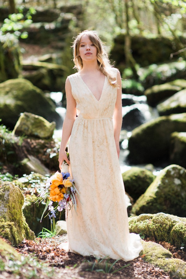 Bride holding bouquet by rocks in woods