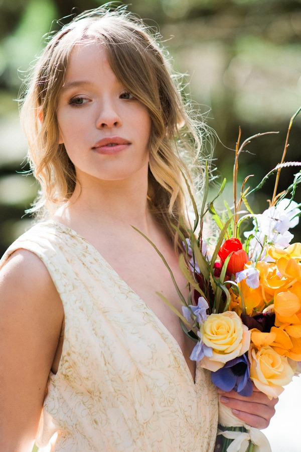 Bride with hair down holding bright bouquet