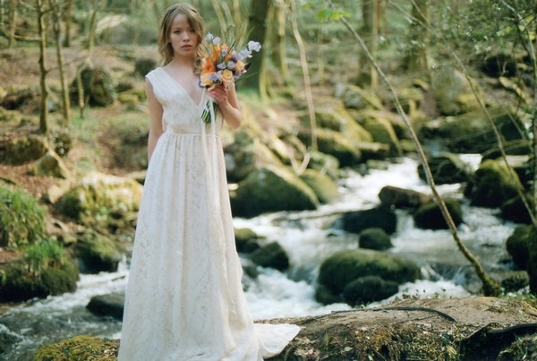 Bride holding bouquet by stream in woods