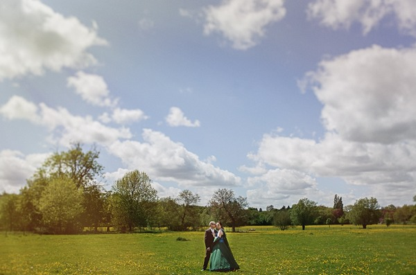 Bride and groom standing in field