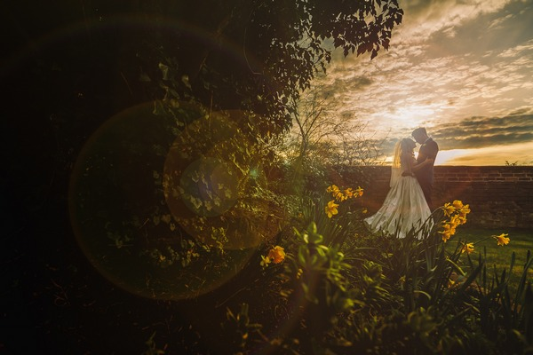 Bride and groom standing in garden as sun sets - Picture by Gareth Newstead Photography