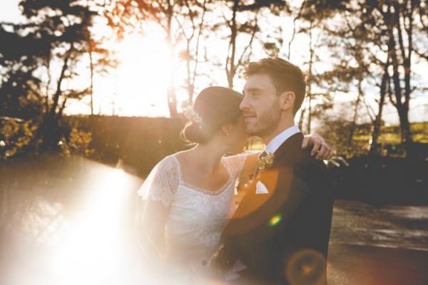 Bride and groom hugging in hazy sunshine - Picture by Claire Basiuk Photography