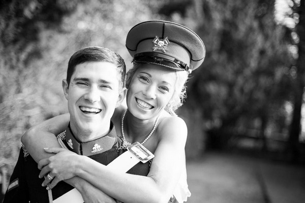 Happy bride and groom with bride wearing groom's military hat - Picture by Snappily Ever After