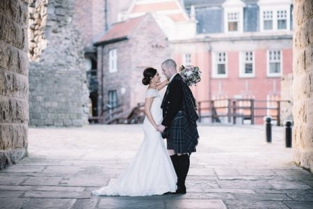 Bride and Scottish groom in kilt facing each other - Picture by Lucie Watson Photography