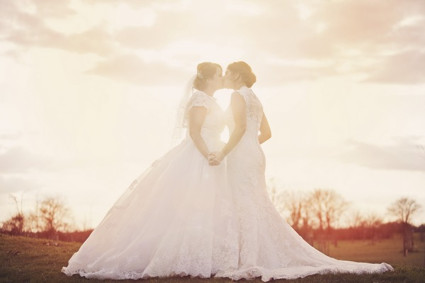 Two brides kissing in hazy sunshine - Picture by Ella Violet Photography