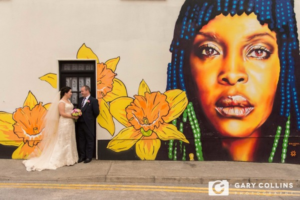 Bride and groom standing by graffiti picture of a woman's face - Picture by Gary Collins Photography