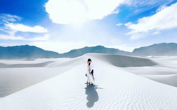 Bride and groom standing on white sand of desert with bright blue sky - Picture by Clane Gessel Photography