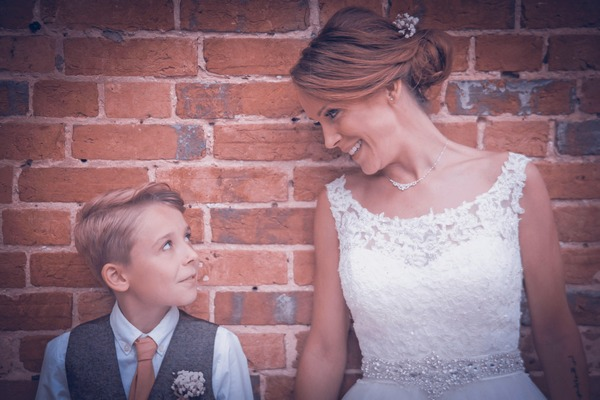Bride and son standing against wall looking at each other - Picture by Simon Emmett Photography